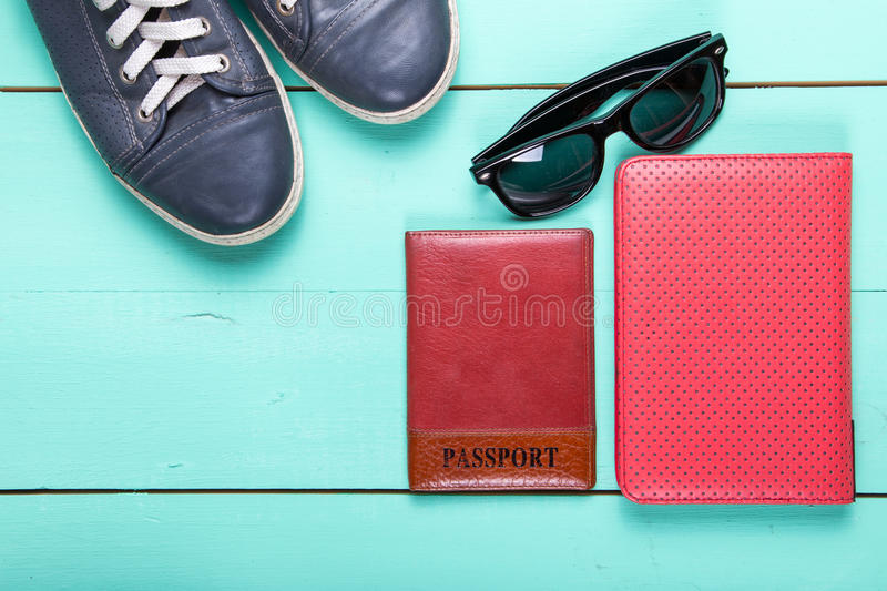 Traveler set top view. Set for traveling, passport, e-book, sneakers, sunglasses. on a wooden turquoise surface, a top view stock photography