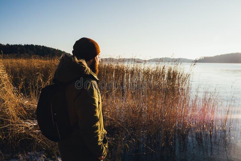 Traveler on the shore of a frozen lake stock photo
