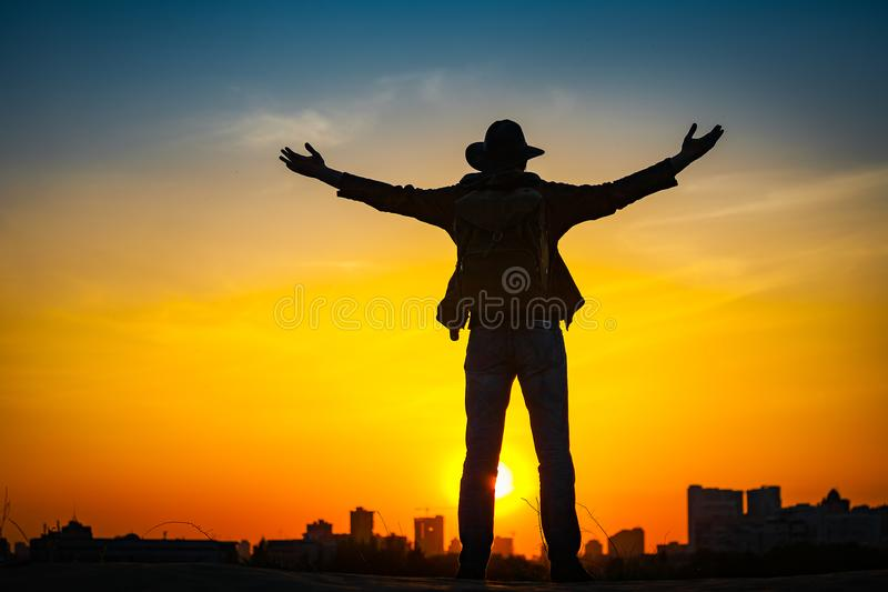 Traveler silhouette with a backpack and cowboy hat royalty free stock image