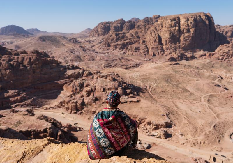 Traveler sitting on edge of mountain cliff, at Wadi Rum desert in Jordan. Travel lifestyle and adventure and journey stock photography