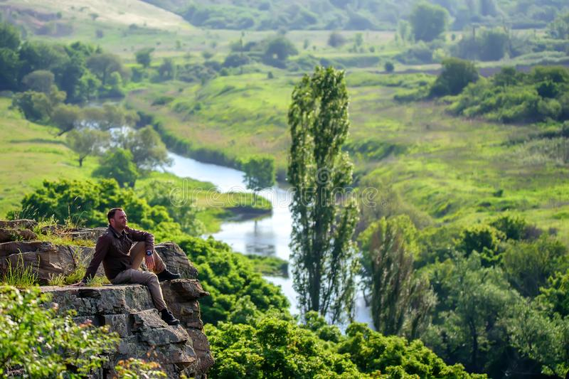 Traveler sitting on edge of rock stock images