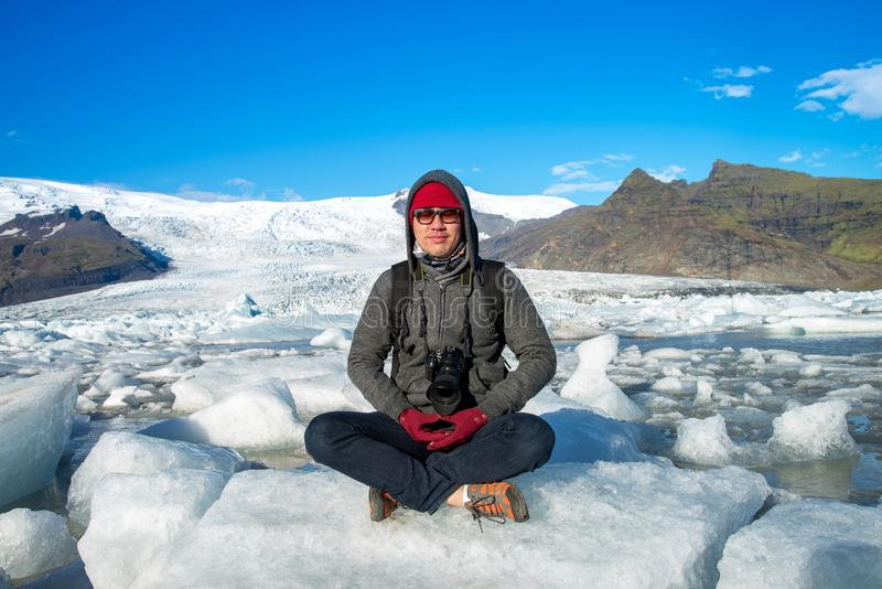 Traveler sitting on small ice shelf and doing meditation. A traveler sitting on small ice shelf and doing meditation at Jokulsarlon Glacier Lagoon in Southeast royalty free stock images