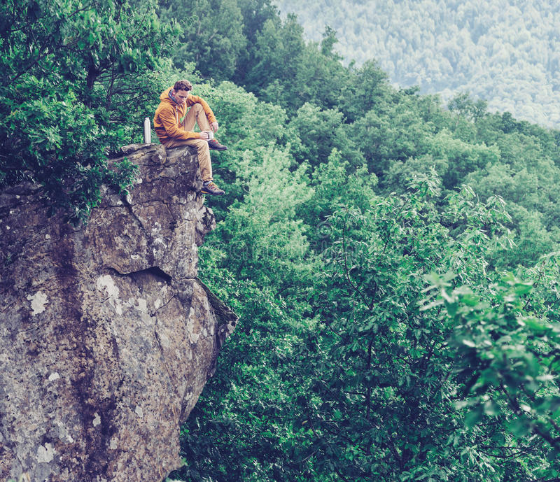 Traveler sitting on top of cliff stock photo