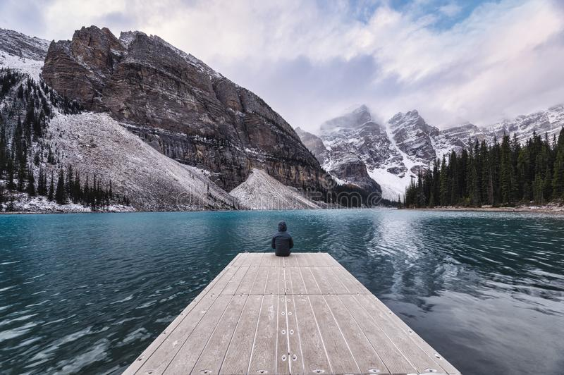 Traveler sitting on wooden pier with rocky mountain in Moraine lake at Banff national park stock images