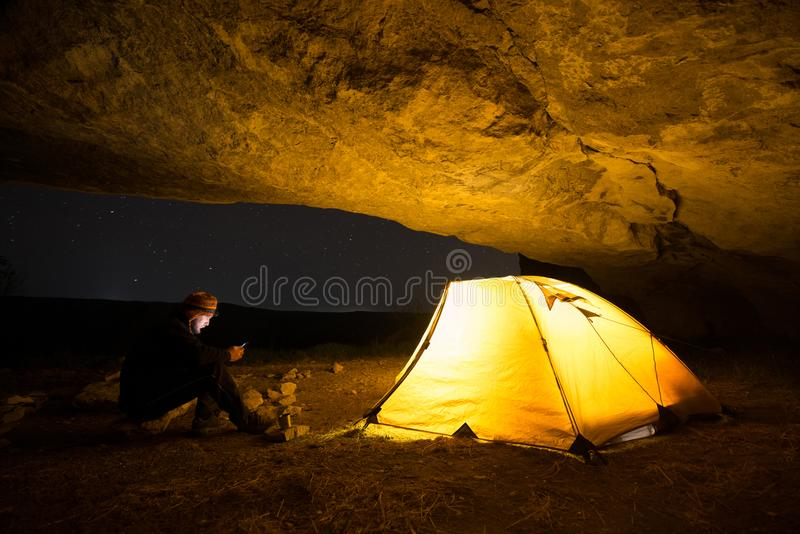 Traveler with smartphone near the glowing camping tent in the night grotto under a starry sky stock photography
