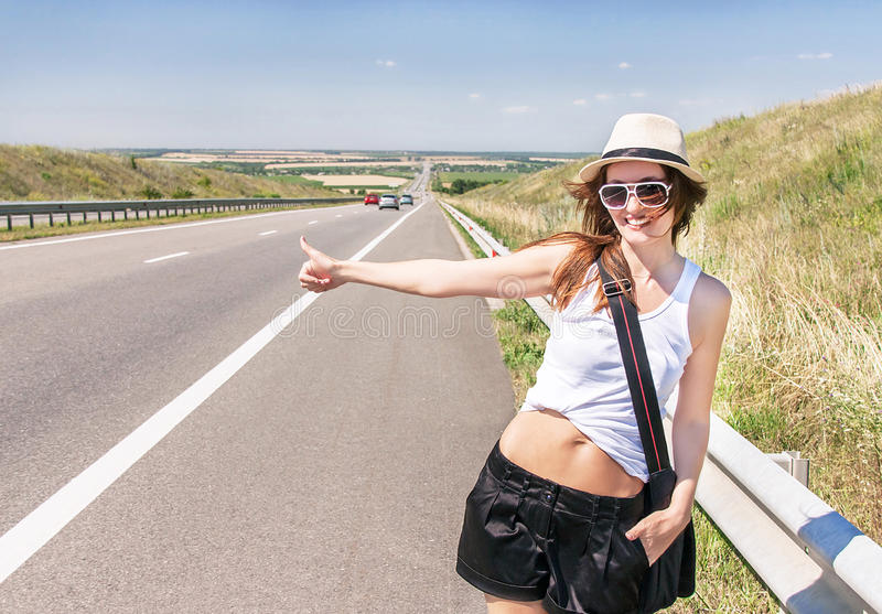 Traveler smiling girl is hitchhiking along a highway. Traveler attractive smiling girl is hitchhiking along a highway (highroad) in the sunny summer day royalty free stock photography
