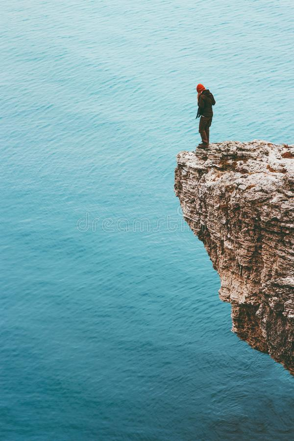 Traveler standing on cliff edge above sea alone Travel Lifestyle concept adventure. Active vacations outdoor solitude emotions stock image