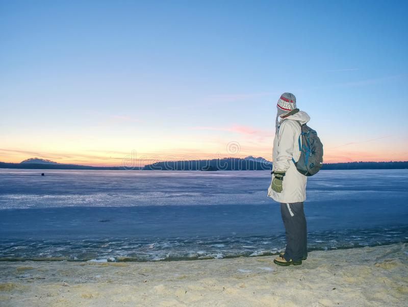 Traveler stay on ice of frozen sea. Woman with backpack. And long warm jacket. Footprints in ice of laggon. Orange sun is rissing above hilly horizon, winter stock photos