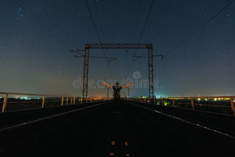 Traveler staying in pose of faith between railways and watching starry sky. Traveler staying between two railways and watching night starry sky. At the night stock photography