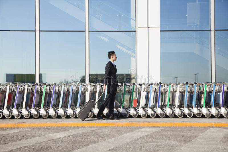 Download Traveler With Suitcase Next To Row Of Luggage Carts At Airport Stock Photo - Image: 31132252