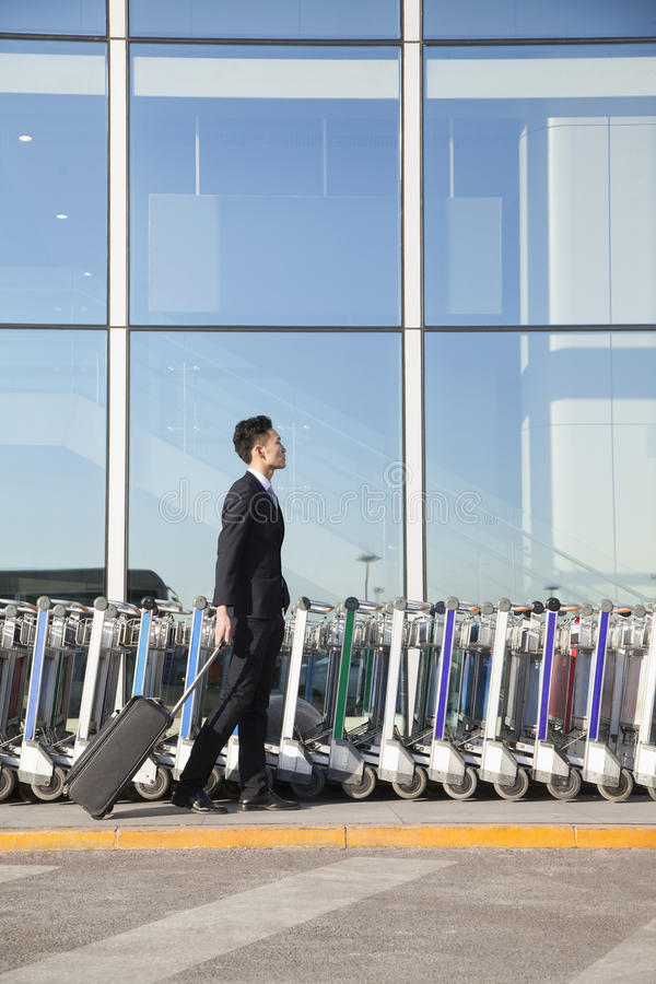 Download Traveler With Suitcase Next To Row Of Luggage Carts At Airport Stock Image - Image: 31695441