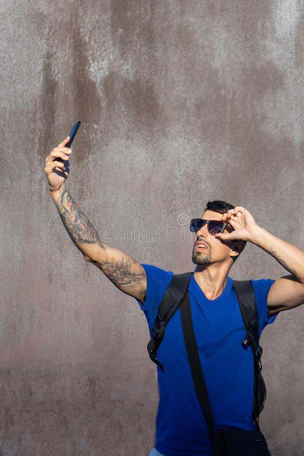 Traveler with tattoos in the arms, lost connectivity and have bad signal in his telephone and hold his sunglasses, search. stock photography