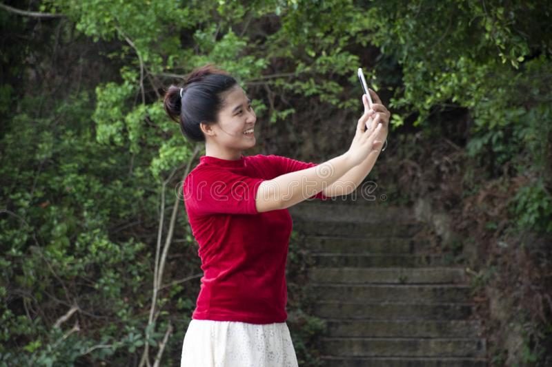 Traveler thai woman use smartphone selfie take photo at view point of Queshi Scenic Area at Shantou town or Swatow city. On May 7, 2018 in Chaozhou, China royalty free stock photos
