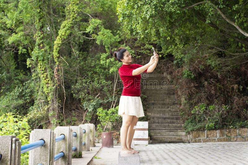Traveler thai woman use smartphone selfie take photo at view point of Queshi Scenic Area at Shantou town or Swatow city. On May 7, 2018 in Chaozhou, China stock photos
