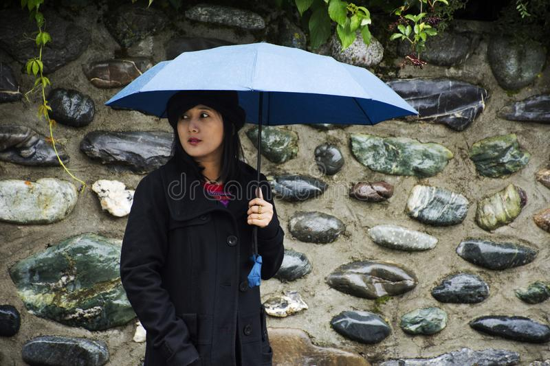 Traveler thai women holding umbrella and walking on the road at raining time stock images