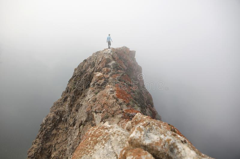 Traveler on top of rock in misty day. stock photo