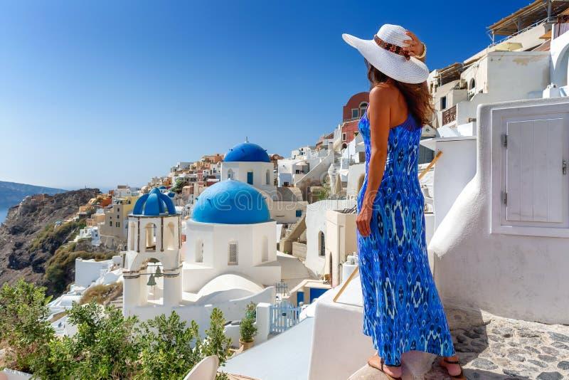 Traveler tourist woman enjoys the view at the village of Oia, Santorini, Greece stock image