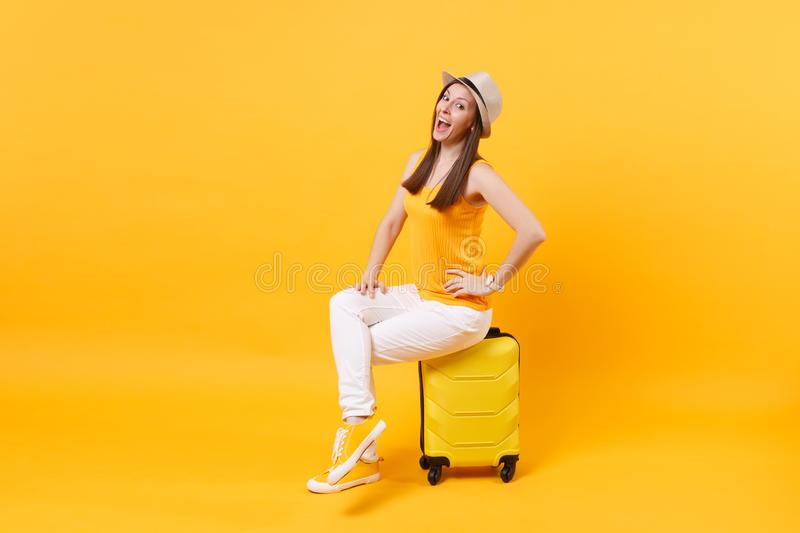 Traveler tourist woman in summer casual clothes, hat sit on suitcase isolated on yellow orange background. Female royalty free stock images