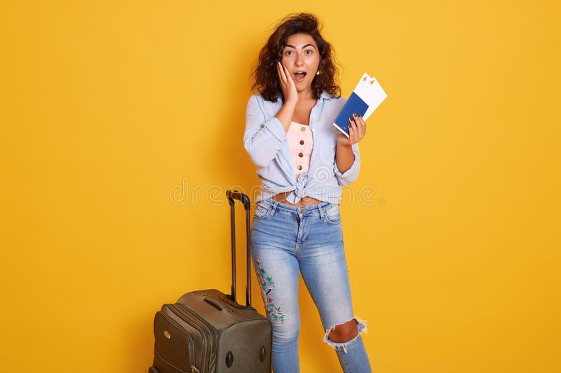 Traveler tourist woman wearing casual clothes standing near her gray suitcase, holding passport and ticket isolated on yellow stock image
