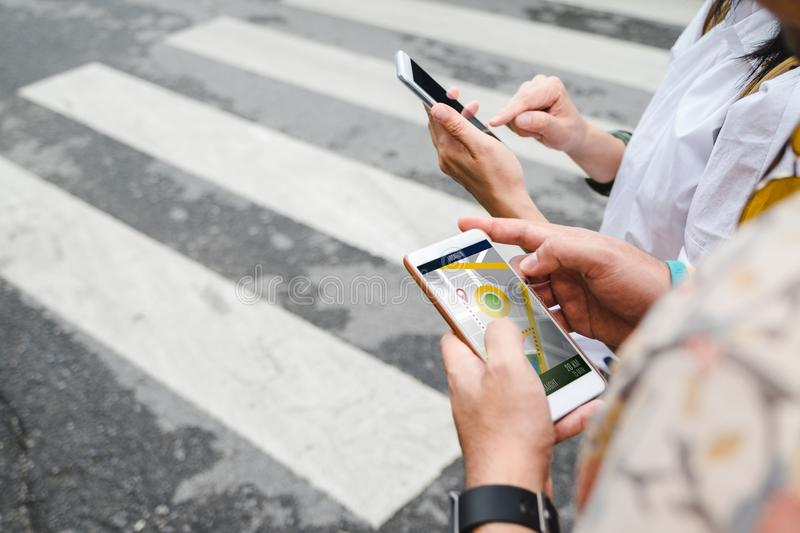 Traveler use map on mobile phone app to search for route location of place with gps on street when travel in city,Technology in l royalty free stock photography