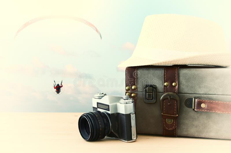 Traveler vintage luggage, camera and fedora hat over wooden table infront of blue sky and parachute sport. holiday and vacation co. Ncept stock photos