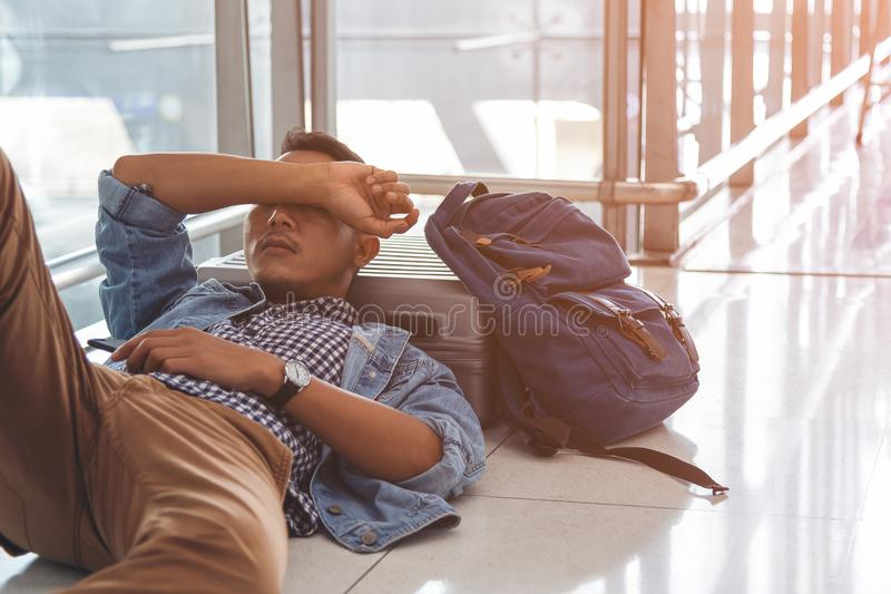 Traveler waiting at the airport departure area for his delay flight.  Young traveler sleeping on the floor with his baggage, stuff stock photography