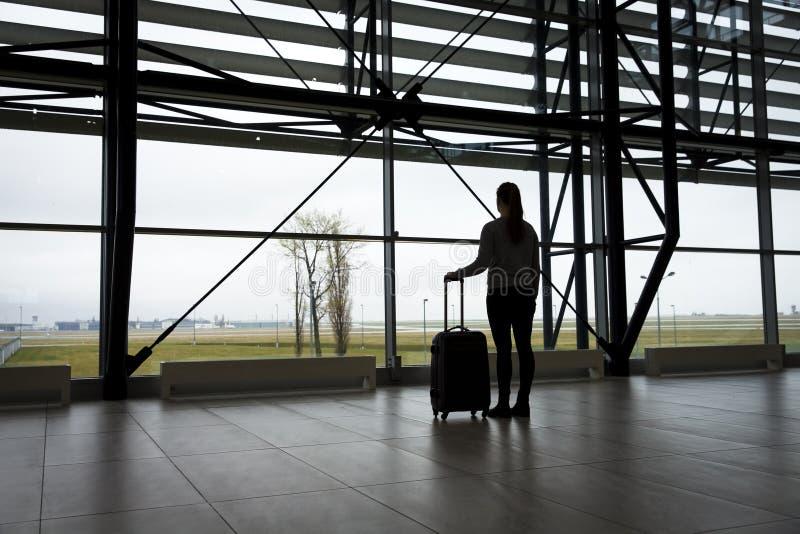 Traveler waiting at airport terminal. Woman waits at airport terminal with a roller bag royalty free stock images