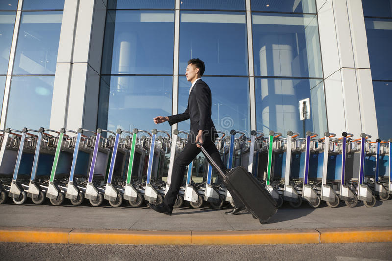 Download Traveler Walking Fast Next To Row Of Luggage Carts At Airport Stock Image - Image: 31132285