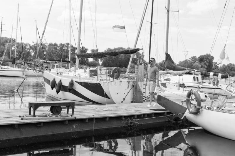 Traveler walking in river marina near of boats with folded sails. Young fashionable man start river journey by yacht. Man and royalty free stock photo