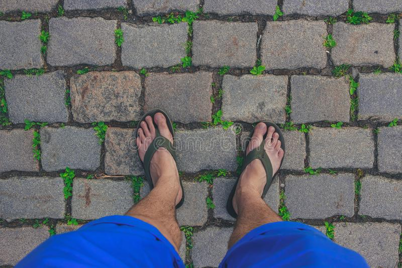 Traveler wearing in flip-flops is walking on a paved path. Man wearing Flip Flops walking down the street on a sunny summer day- closeup of the feet stock photo