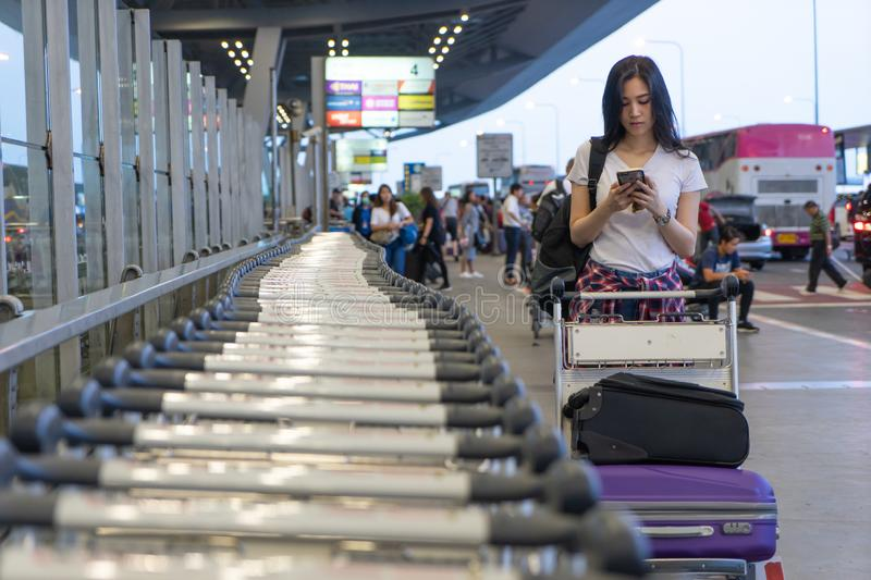 Traveler woman in airport terminal using mobile smartphone with luggage and bag on airport trolley cart with busy airport. Passengers crowd in background at stock photography