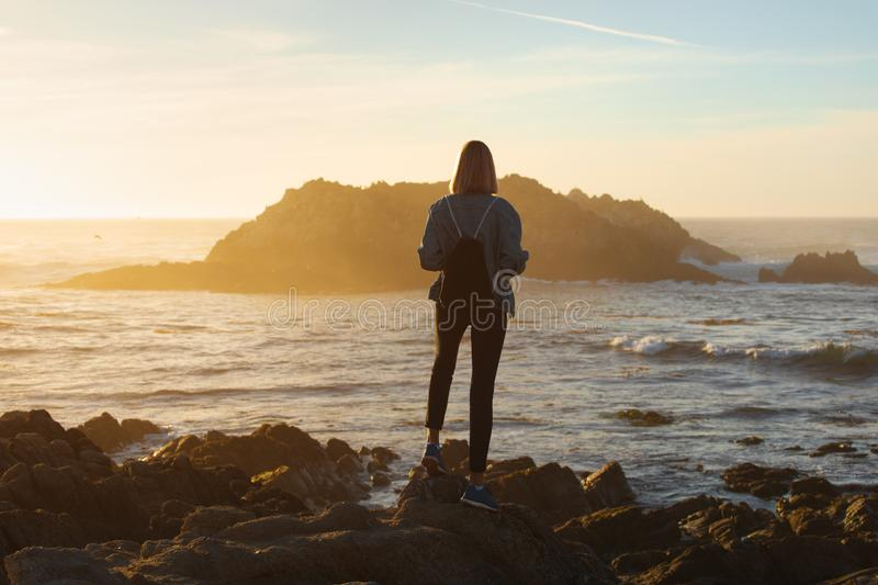 Traveler woman with backpack enjoying ocean view, girl hiker at sunset, travel concept, California, USA royalty free stock photos