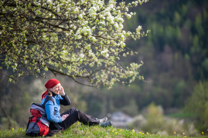 Traveler woman with a backpack near blooming tree. Happy female with a backpack relax under blooming tree on top of hill with yellow wildflowers, green grass and royalty free stock image