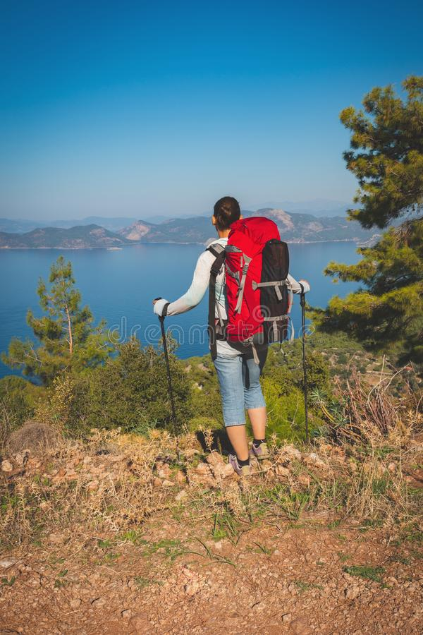 Traveler woman with backpack stands on the cliff royalty free stock photography