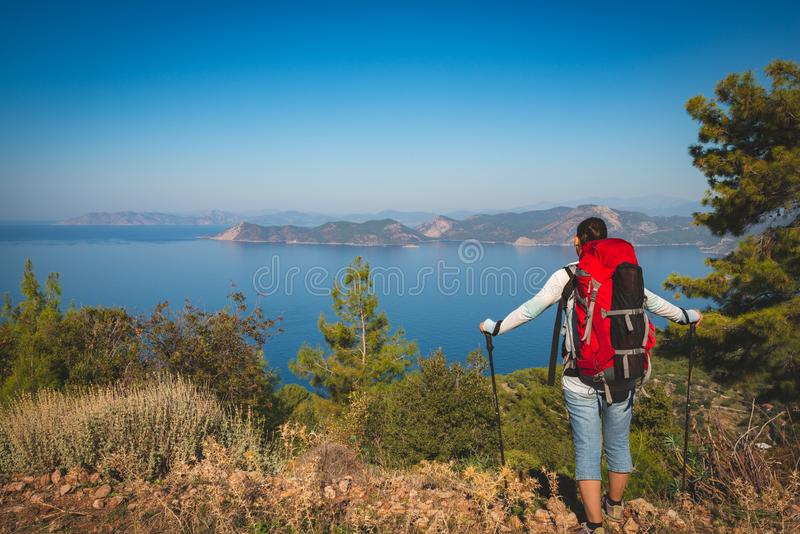 Traveler woman with backpack stands on the cliff stock images
