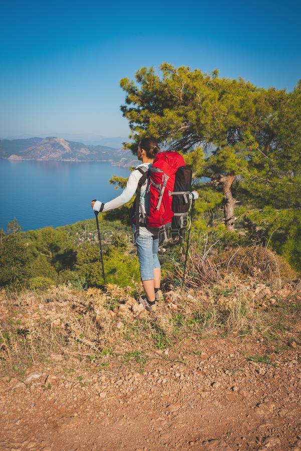 Traveler woman with backpack stands on the cliff royalty free stock image