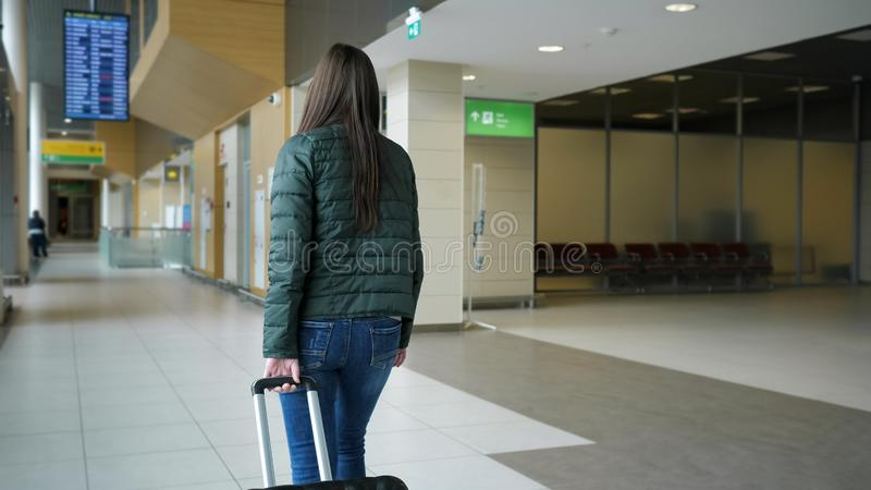 Traveler woman is walking in modern airport terminal carrying suitcase, back view. royalty free stock photos