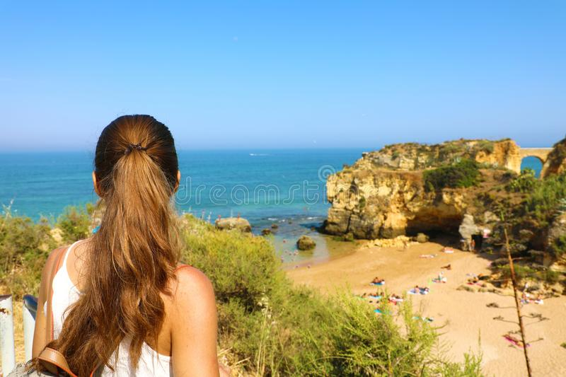 Traveler woman enjoying and relaxing stunning view of Southern Portugal. Back view of beautiful girl in her travel in Lagos. Algarve, Portugal. Summer vacation royalty free stock image
