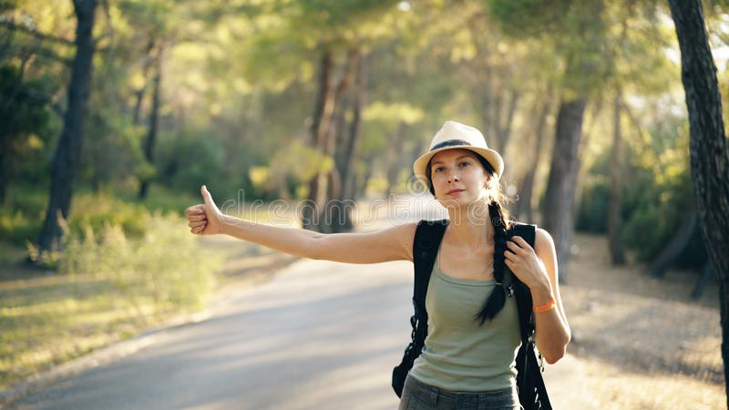 Traveler woman hitchhiking on a sunny forest road. Tourist girl looking for ride to start her journey royalty free stock photos
