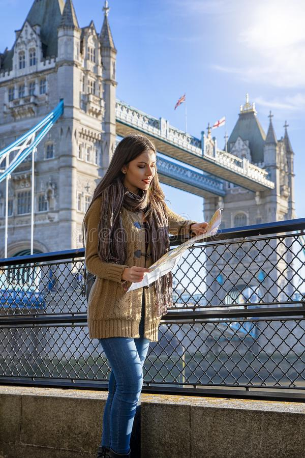 Traveler woman holds a map in front of Tower Bridge London. Beautiful traveler woman holds a map in front of Tower Bridge London during her sightseeing trip royalty free stock image