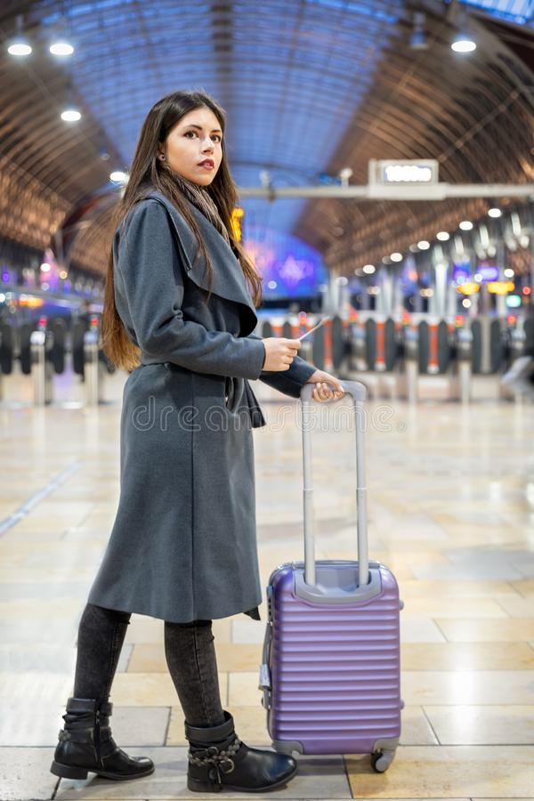 Traveler woman with luggage waiting on a train station. Attractive traveler woman with luggage waiting on a train station for the train royalty free stock photo