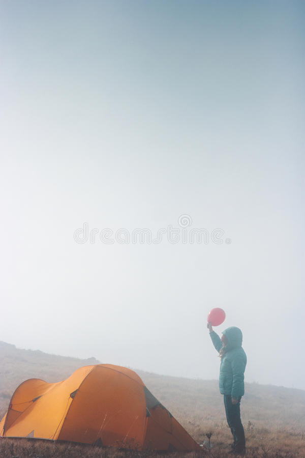 Traveler woman with red balloon and tent camping. Travel Lifestyle concept adventure vacations outdoor stock photography