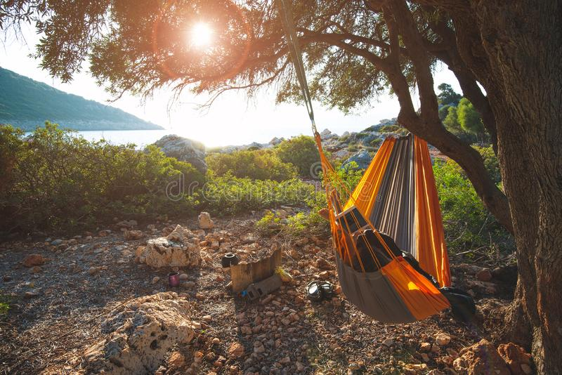 Traveler woman relaxes in a hammock on a rocky seashore stock photo