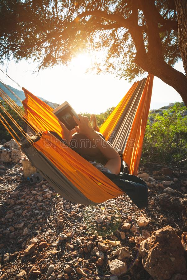 Traveler woman relaxes in a hammock on a rocky seashore royalty free stock images