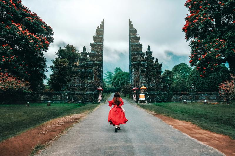 Traveler Woman Running at the Gates Hindu temple Bali, Indonesia stock photo