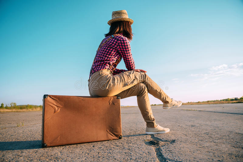 Traveler woman sits on suitcase on road royalty free stock images