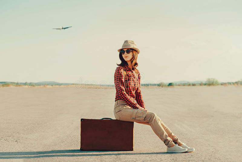 Traveler woman sitting on suitcase on road royalty free stock photo