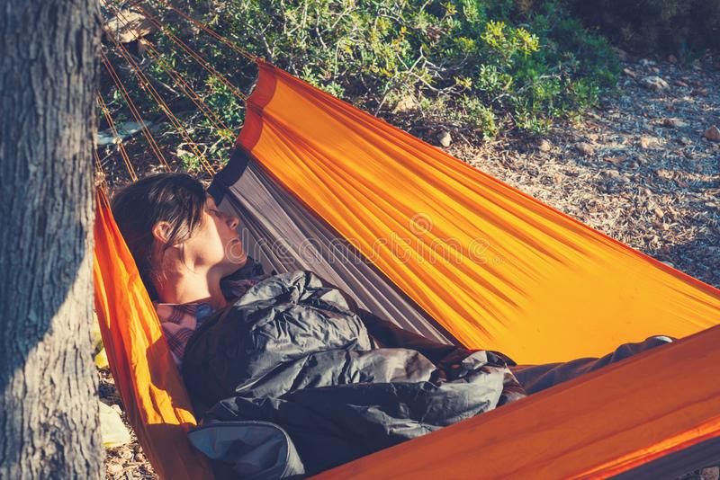 Traveler woman sleeping in a hammock on a rocky seashore stock photography