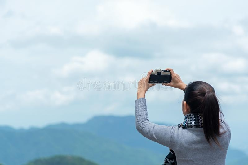 Traveler woman taking photo with her phone of the view natural mountain in the winter day morning, royalty free stock photos