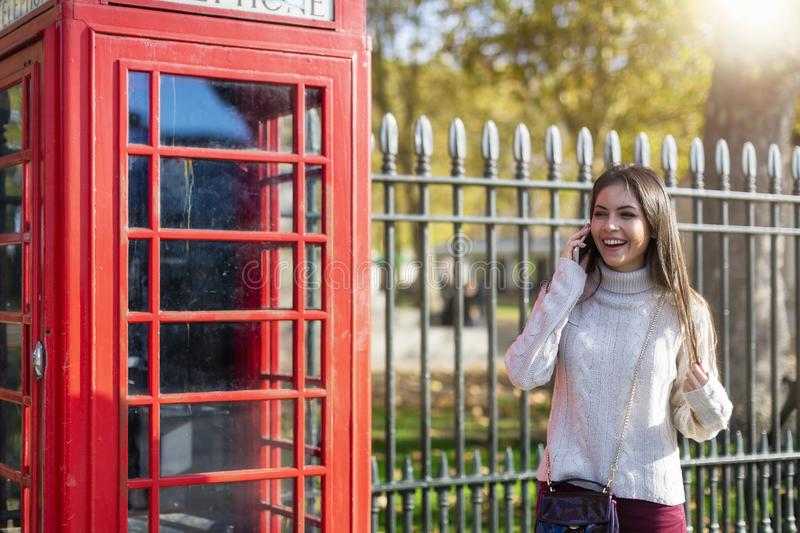 Traveler woman talks on her cellphone next to a red telephone booth in London, UK. Pretty traveler woman in casual clothing stands next to a red telephone booth royalty free stock photos